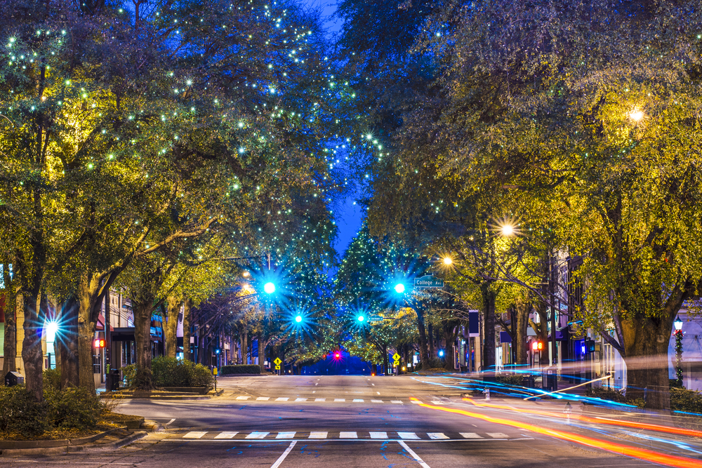 A street at night that is lit up by the bright white and blue Christmas lights at night in Athens, Georgia.