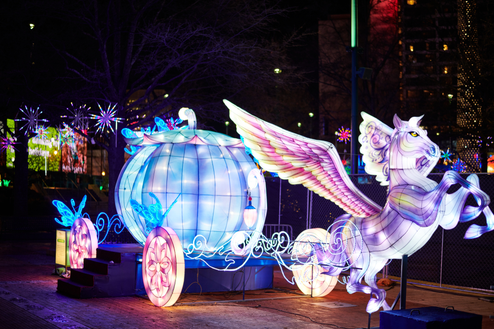 A picture of a handmade Christmas display of a Pegasus and carriage lit brightly at the Chinese Lantern Festival.