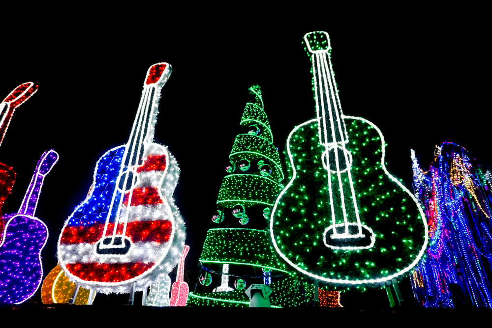 A photo of two Christmas light displays shaped as guitars with colorful Christmas lights and tree in the background.