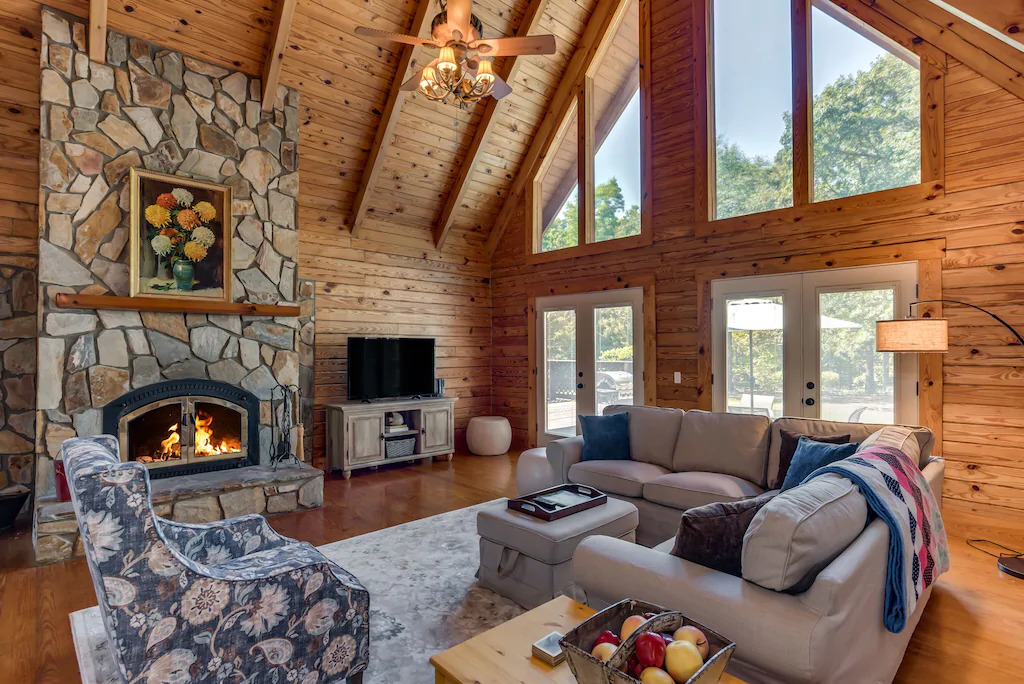 Photo of the interior of Cider House with a tall stone fireplace, modern sofa, and rustic wood walls and large windows