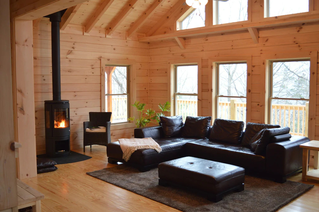 Photo of a cabin with raw wood walls, a modern black leather sofa, and modern wood burning fireplace at the Chalet at Windhaven, one of the best Blue Ridge Mountains cabins.