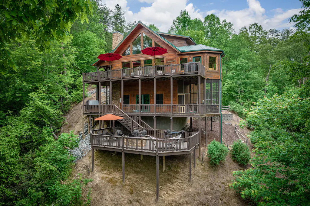 Photo of a 3 story log cabin with wrap around decks built onto the side of a hill and surrounded by trees.