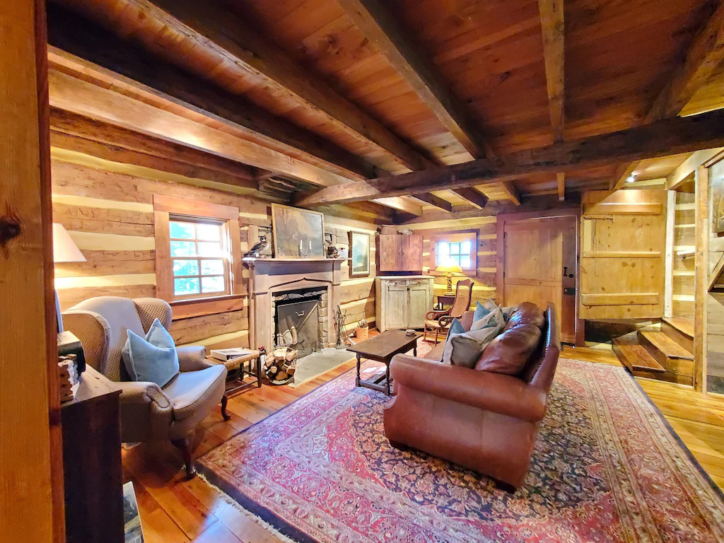 Photo of the interior of Overlook Cabin, one of the coziest Blue Ridge Mountains cabins featuring wood beams on the ceiling, a stone fireplace and leather sofa.