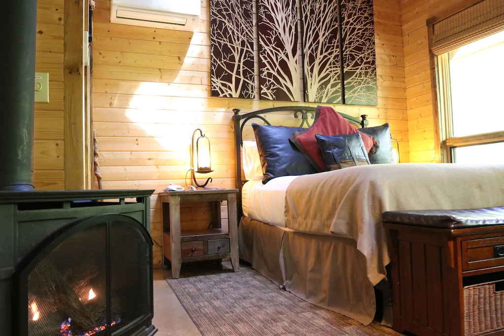 Phot of a bed inside of a rustic wood cabin with a vintage wood burning fireplace next to it