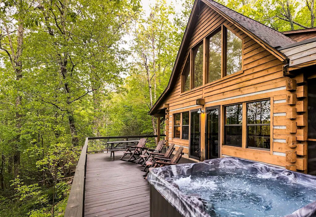 Photo of the deck outside of a log cabin with a  hot tub and Adirondack chairs overlooking the trees.