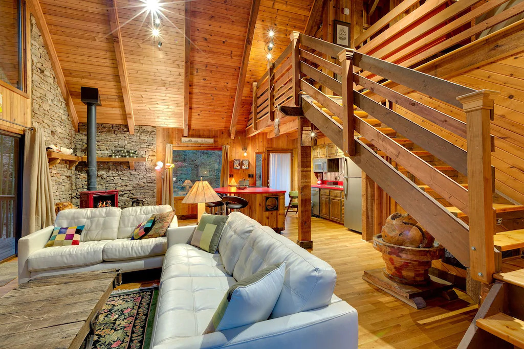 Phot of modern white sofas inside a cabin with a wood interior with a stone fireplace at River Rock Cabin, one of the best Blue Ridge Mountains cabins