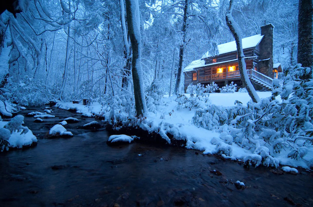 Phot of a log cabin nestled on the banks of a river surrounded by trees and covered in sow