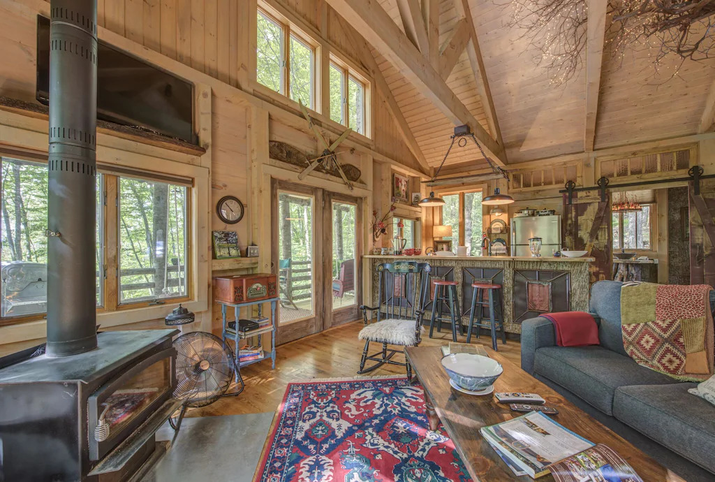 Phot of a rustic cabin interior with wood walls and beams, eclectic furnishings, and a vintage style wood burning fireplace.