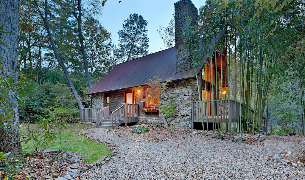 Photo of a cabin with stone exterior surrounded by trees in the blue Ridge Mountains
