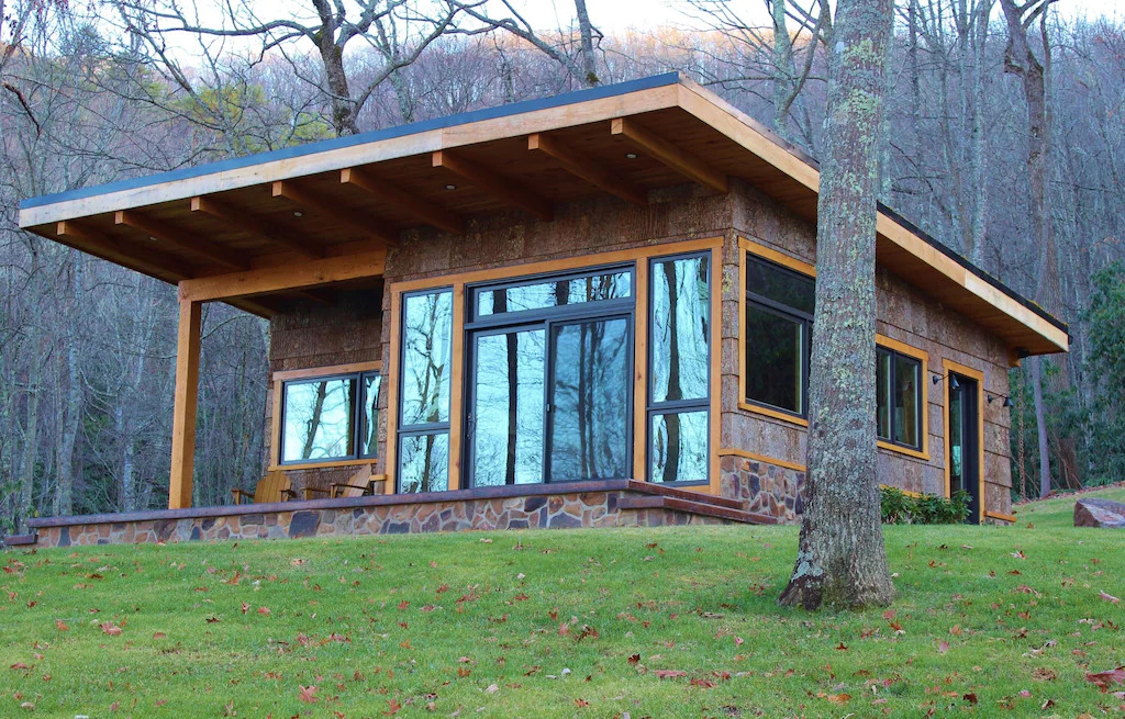 Photo of a modern cabin with sloped roof and large windows surrounded by trees