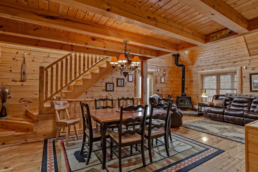 Photo of the interior of Creekside Cabin with raw wood walls, wood burning stove. a large dining table, and leather sofa