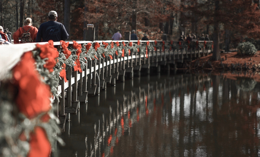 A photo of people crossing a bridge decorated in garland and red Christmas bows in the autumn located in the Callaway Gardens in Georgia.
