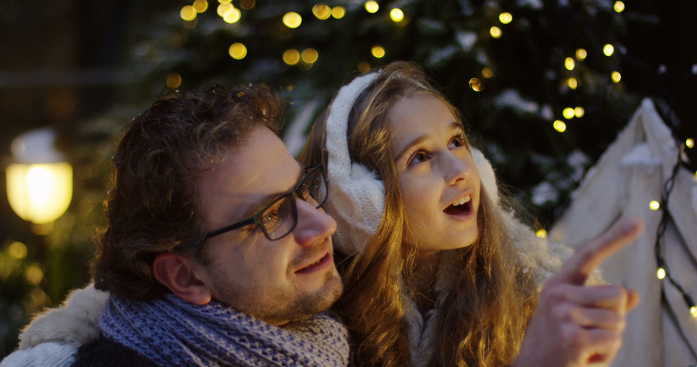 A photo of a father holding his daughter as he points at Christmas lights on a cold night.