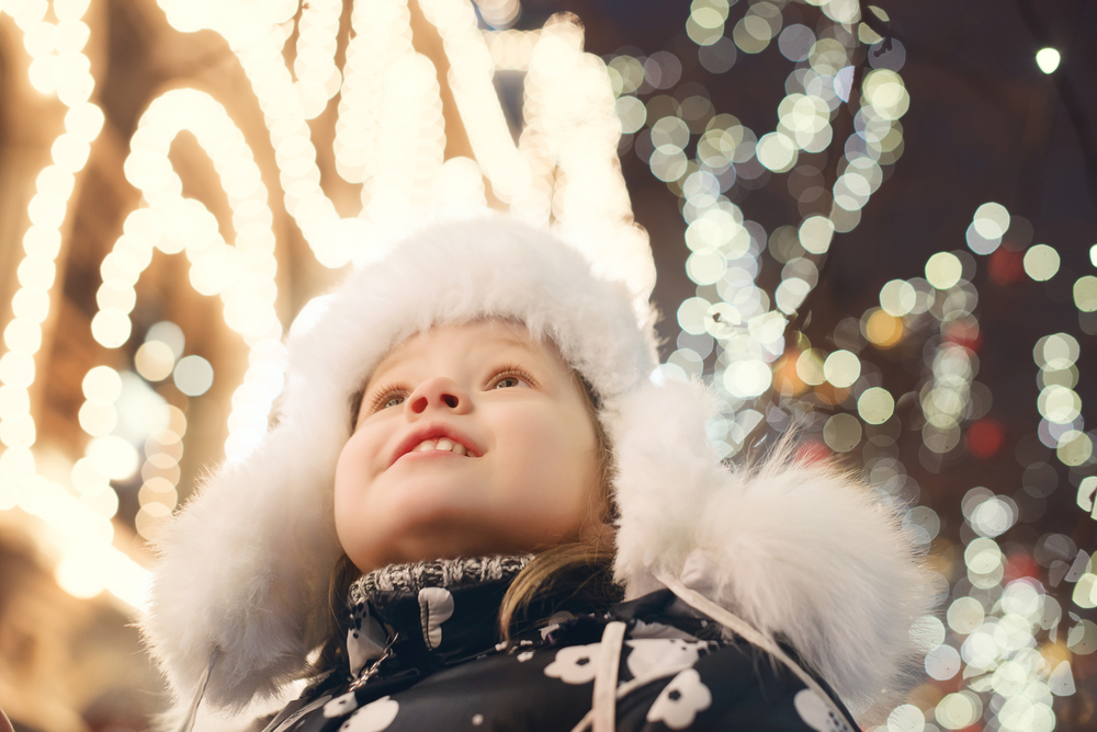 A picture of a small child in a heavy coat looking up at sparkling Christmas lights.