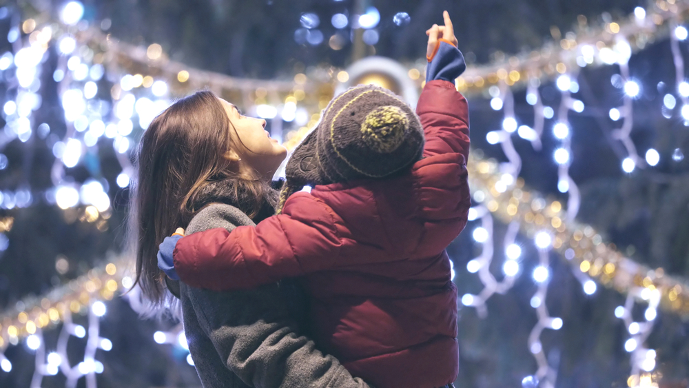 A photo of a mother holding her child as they point up at Christmas lights glowing in the background.