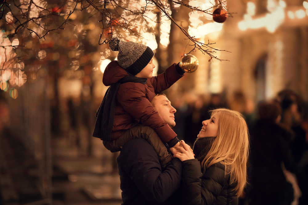 A picture of a child touching a tree ornament while sitting on top of their fathers shoulders as the mother smiles at them.