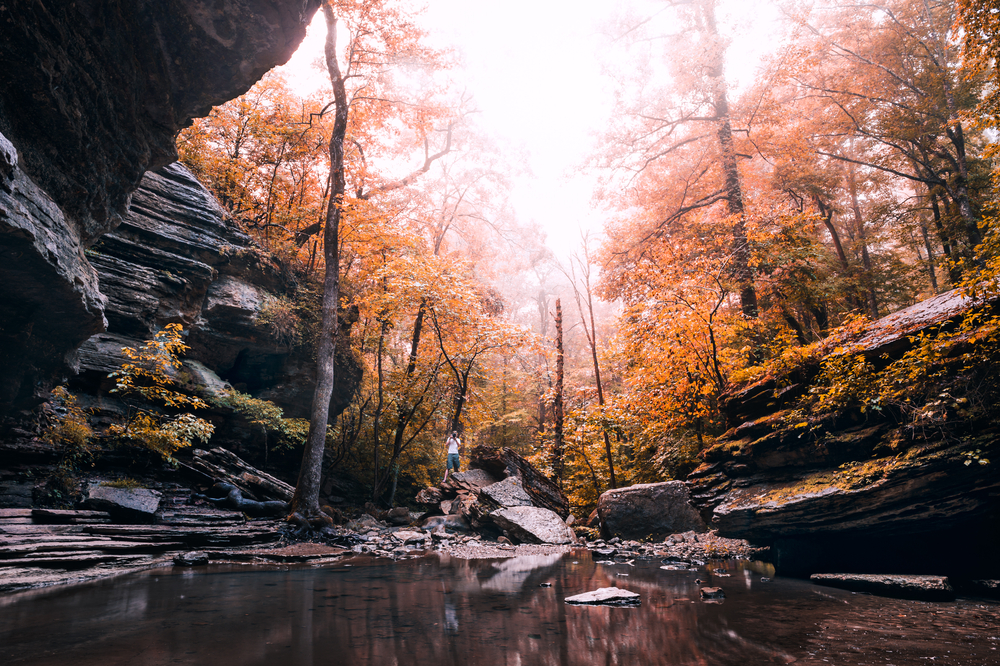 A picture of a photographer taking a picture of the pool of water from Eden Falls surrounded by rock formations and trees covered in orange fall leaves.