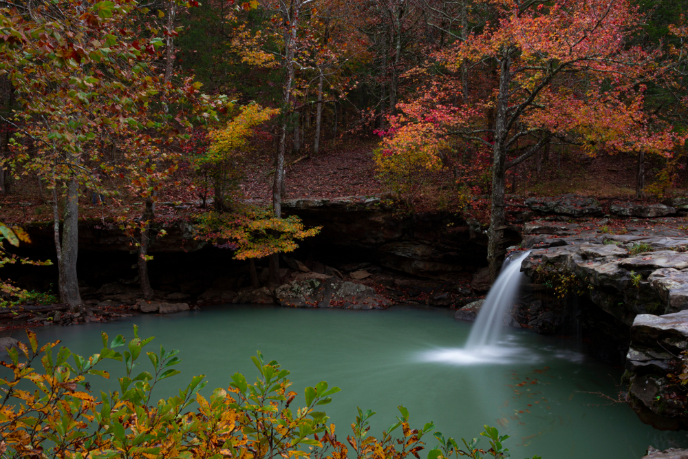 A photo of Falling Water Waterfall pouring into it's pool of blue water with the the trees decorated in fall foliage.