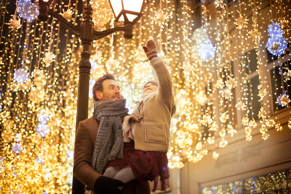 A father holding his daughter who is smiling and pointing at the dangling Christmas lights.