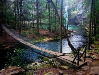 A picture of a suspension bridge and river flowing from the Foster Falls waterfall in South Cumberland State Park in Tennessee.