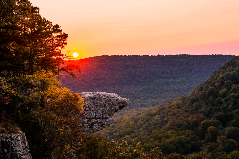 A picture of a sunrise over the protruding Hawksbill Crag that is overlooking the forests of Whitaker Point in the autumn.