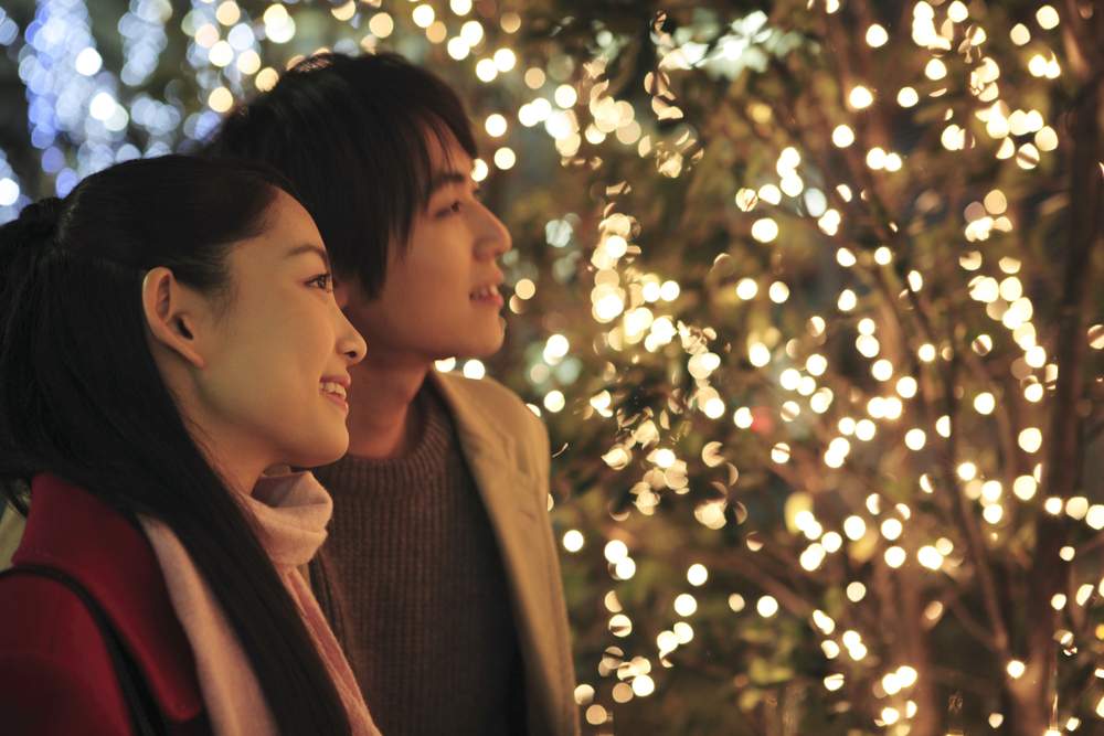 A couple smiling as they look at Christmas lights that illuminate their faces.