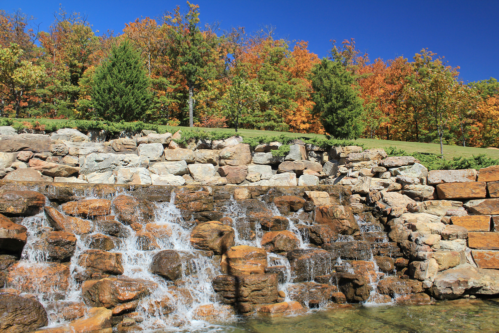 A picture of a rocky waterfall in front of a forest of trees with fall colored leaves on a sunny day.