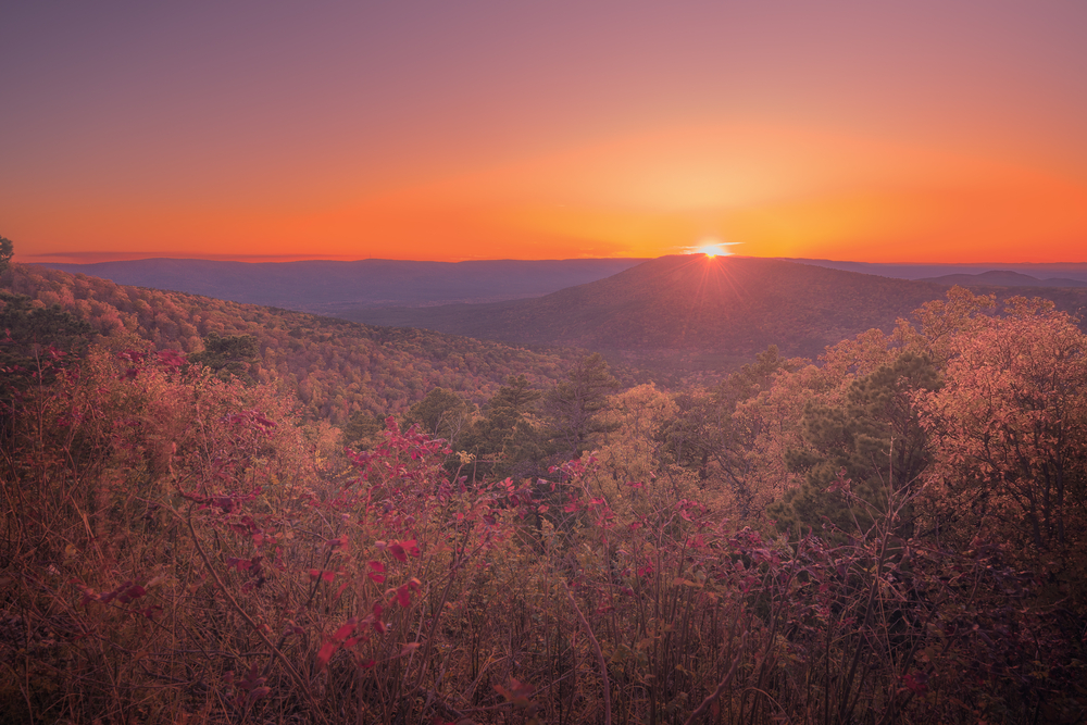 A photo of an orange sunset over the rolling Ozark Mountains in the fall.