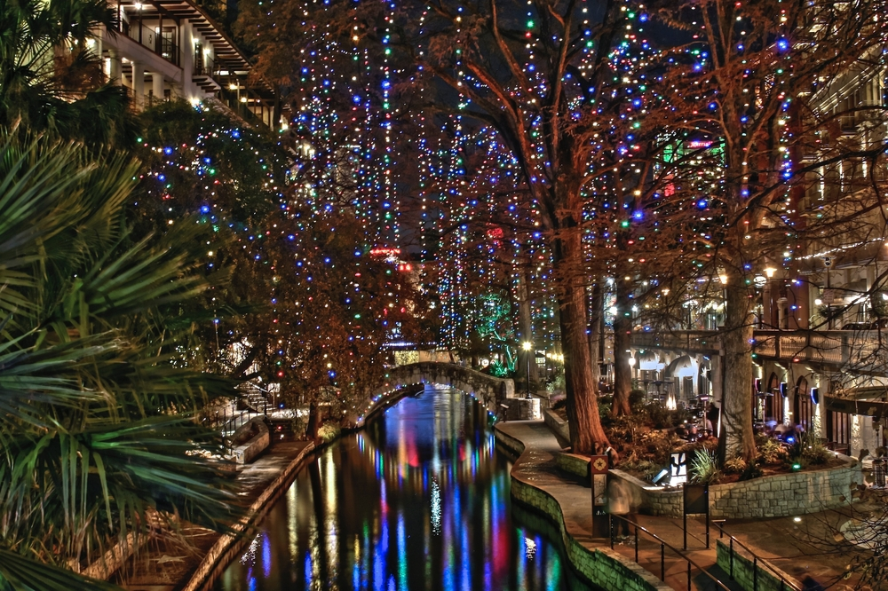 A photo of the San Antonio Riverwalk decorated with Christmas lights that reflect on the river.