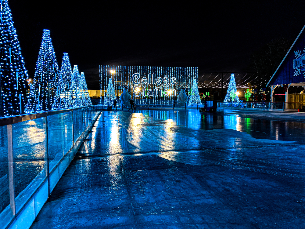 A picture of an ice skating rink reflecting blue light from the surrounding Christmas lights and decorations.