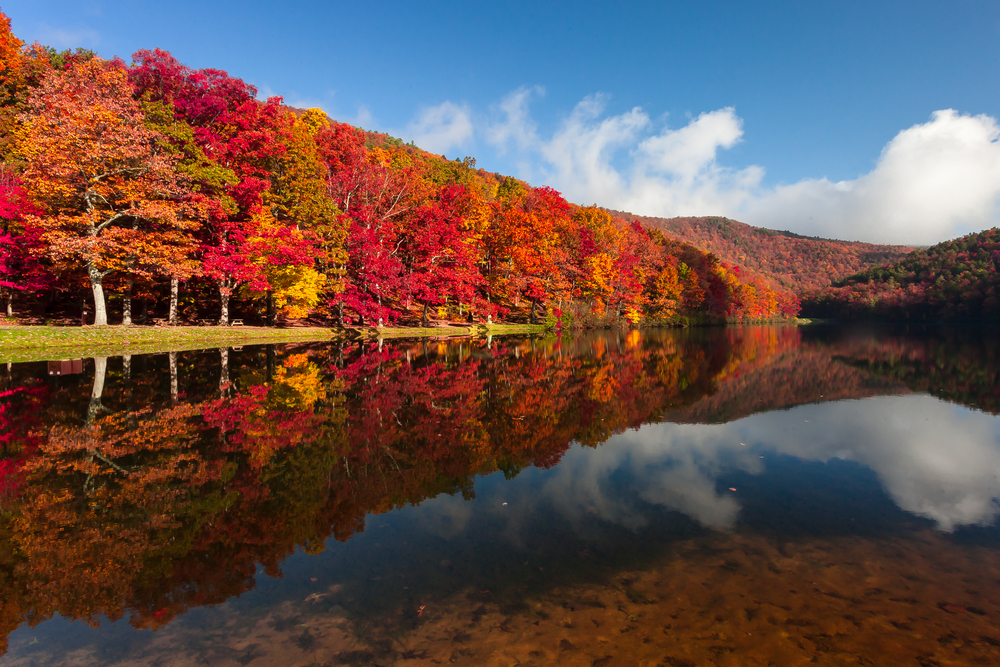 Fall foliage reflected in Sherando Lake in George Washington National Forest, one of the best places to experience fall in Virginia.