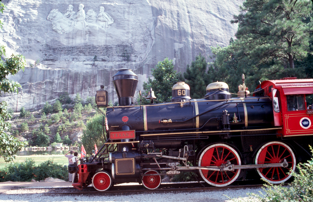 A photo of a red and black train in front of the carved men and horses on Stone Mountain in Georgia.