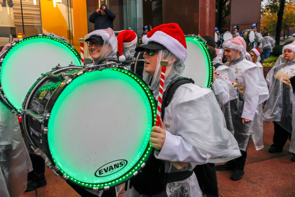A photo of a marching band wearing Santa hats with drums that are decorated in green lights.