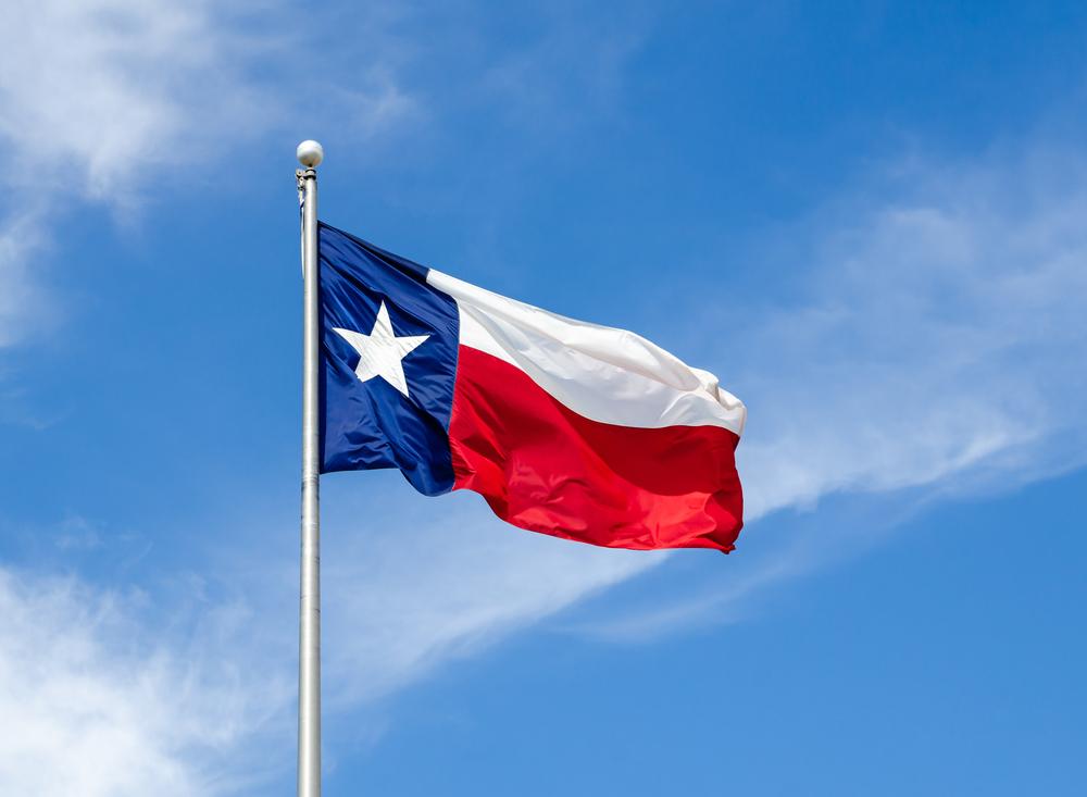 The Texas flag waves on a flag pole on a windy day.