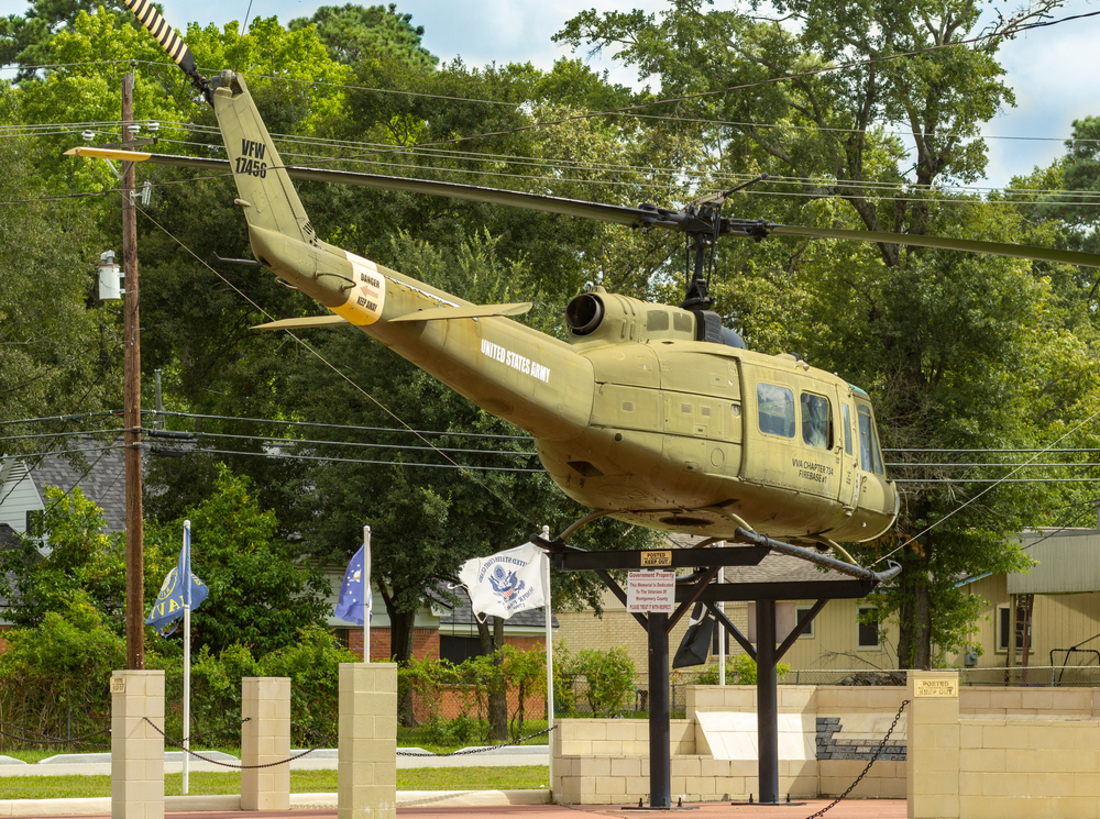 A military helicopter is displayed behind several military flags on the VFW Hall in Conroe, Texas.