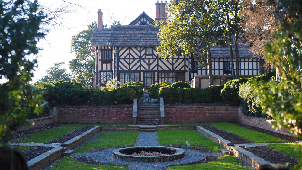 Photo of Agecroft Manor, a Tudor style home with a grand courtyard surrounded by trees.