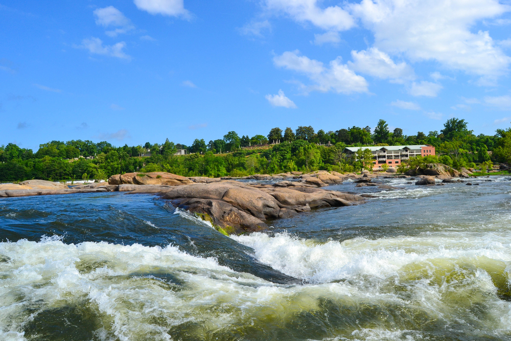 Photo of rapids on the James River with large boulders in the water and Belle Isle in the background.