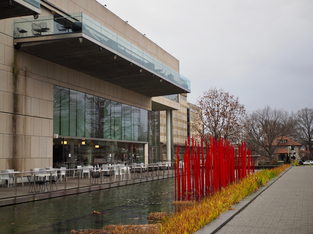 Photo of the entrance of the Virginia Museum of Fine Arts with café tables and a sculpture in a pond outside.