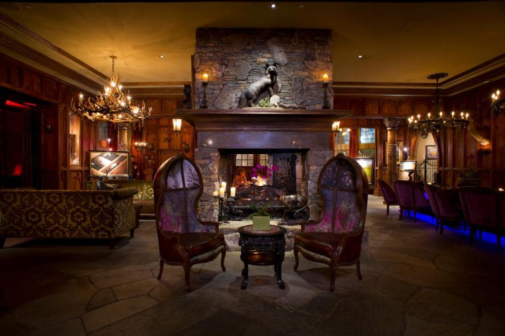 Photo of the European old-world style lobby inside The Grand Bohemian Hotel, featuring dark wood walls, a stone fireplace, an antler chandelier, and antique furniture.