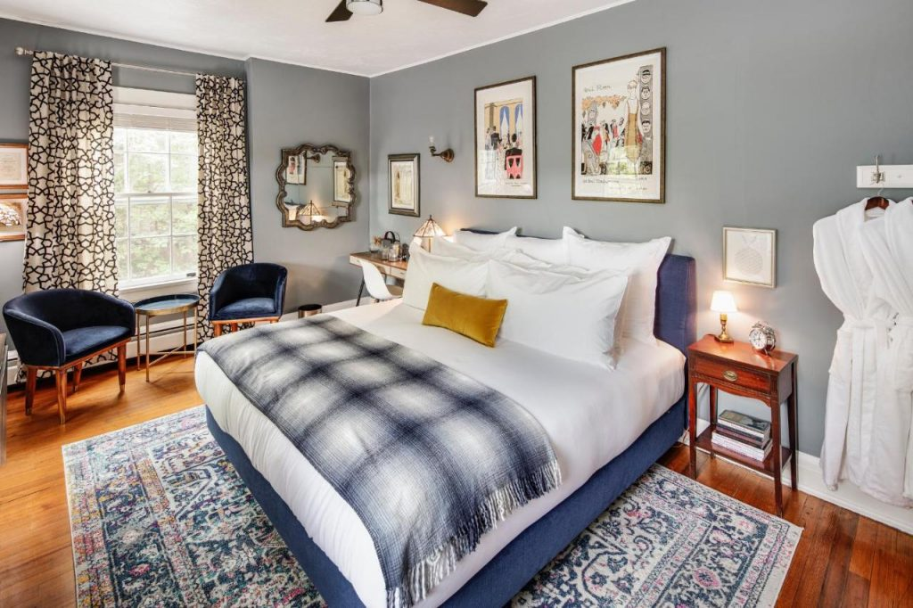 Photo of a bedroom at Applewood Manor with modern blue bed frame, blue velvet and gold chairs, a patterned rug, and white linens.