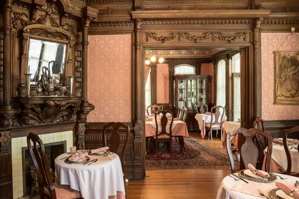 Photo of the dining room inside the cedar crest Inn featuring antique wooden dining tables with white tablecloths, vintage wallpaper, and dark wood trim.