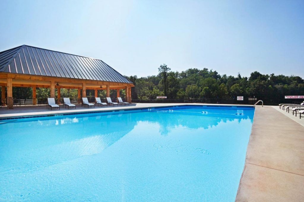 Photo of a large outdoor swimming pool next to a wooden gazebo at the Crowne Plaza.