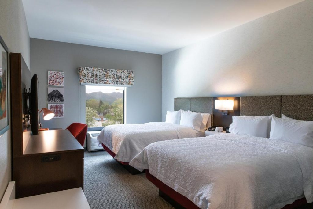 Phot of a room inside the Hampton Inn black mountain with two queen size beds with white linens, a desk area with red chair, and view of the mountains outside the window.