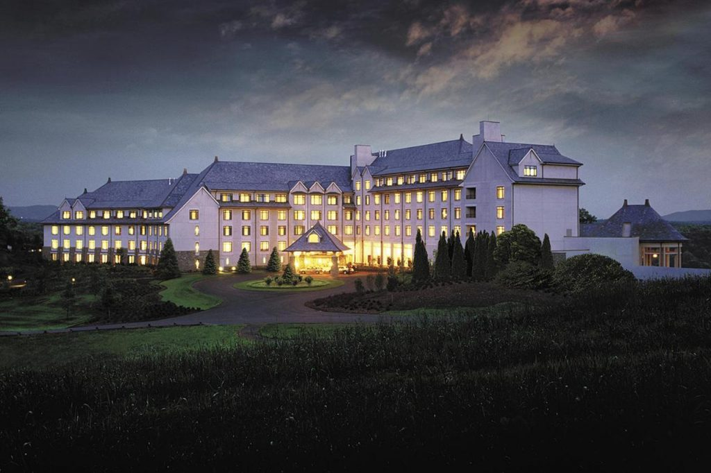 Phot of the exterior of The Inn on the Biltmore, a very large building with a white exterior surrounded by lush green grounds. This is where to stay in Asheville for luxury.