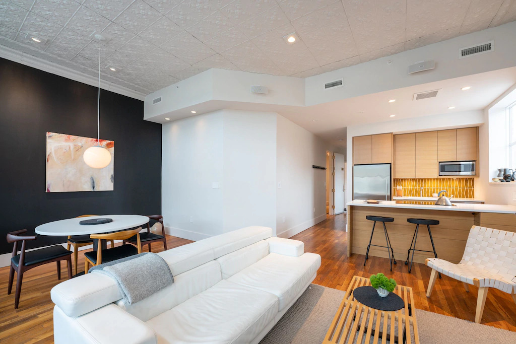 Photo of the living area with modern white sofa, kitchen, with light wood cabinets and bright yellow backsplash, and dining area with black wall inside The Sinclair vacation rental.