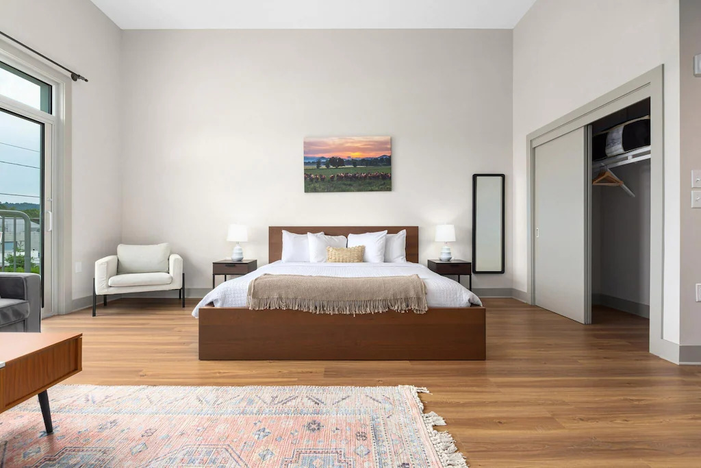 Photo of a modern bedroom area with wood bed frame, colorful rug, and white modern chair at River Row Flats.