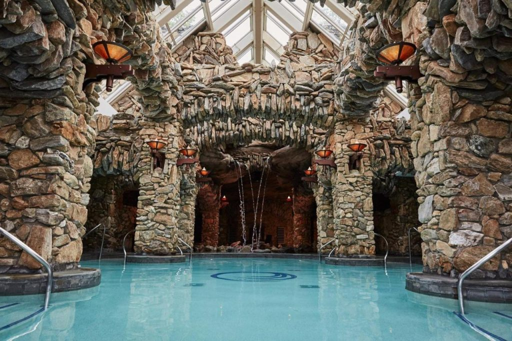 Photo of an indoor spa pool with rock arches and columns built around it at The Omni Grove Park Inn.