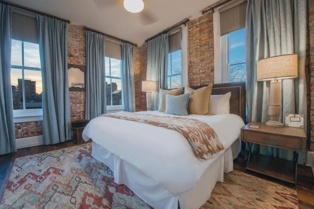 Photo of a room inside the Windsor with old brick walls, a colorful area rug, and bed with colorful pillows.