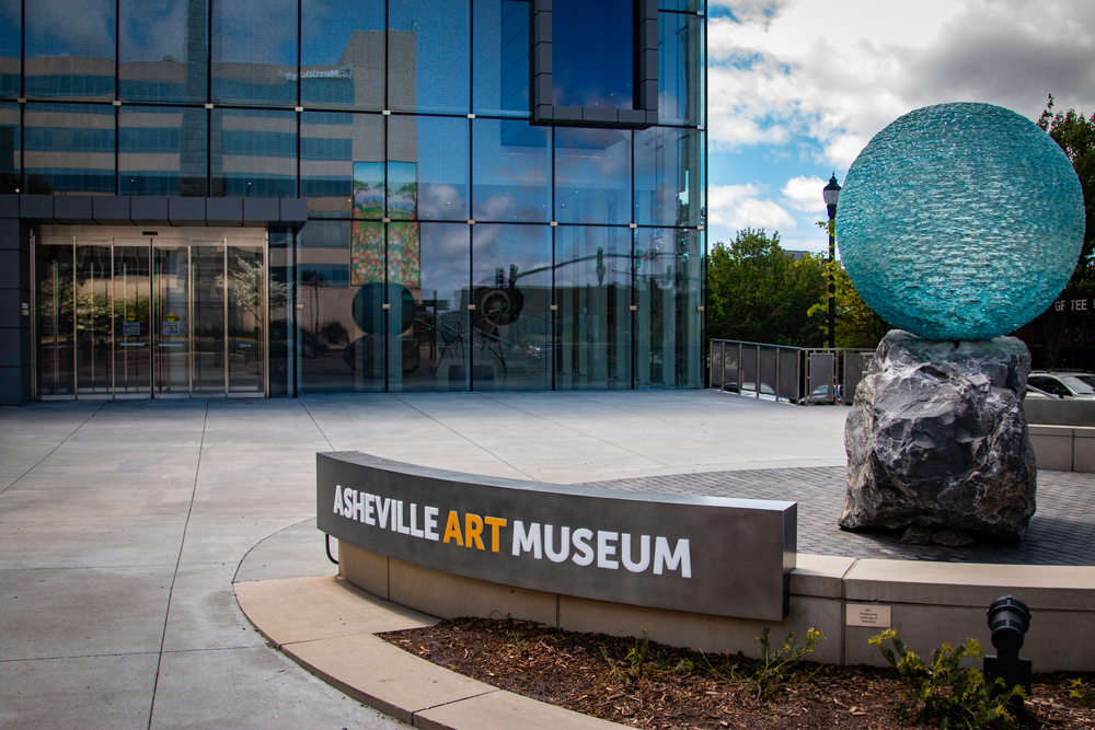 The exterior and sign of the Asheville Museum of Art. The building seems to be made entirely of glass windows. The sign is on the ground in a courtyard with the word 'art' in yellow and 'Asheville' and 'museum' in white. Behind the sign is a sculpture that is a large boulder with a blue glass ball perched on top of it.