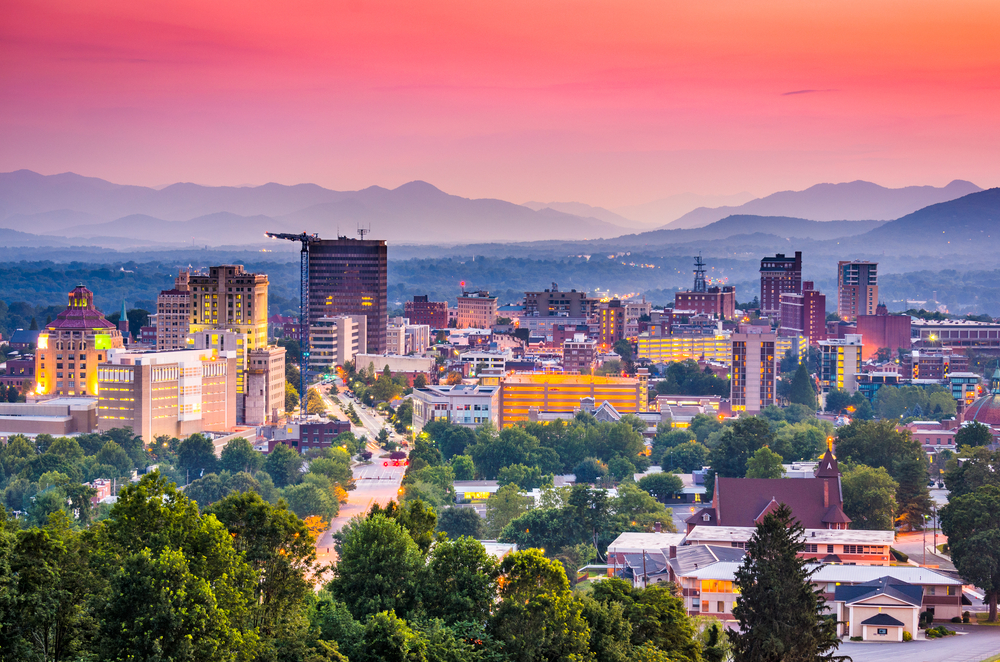A view of the Asheville skyline. It is twilight so the sky is pink, purple and blue. At the front of the image you can see the skyline with buildings all lit up and trees scattered around the city. Behind the city you can see the Blue Ridge Mountains which are almost in silhouette in a pale dark blue and purple.